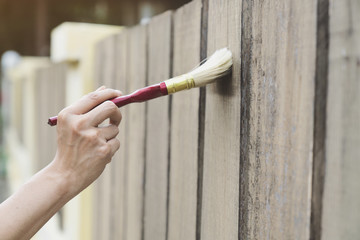 Applying protective varnish on wooden fence, diy and repair house concept