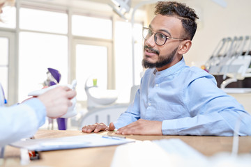 Portrait of modern Middle-Eastern man talking to dentist sitting at desk in modern dental clinic, copy space