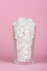 Drinking glass of of lump sugar cubes on pink pastel background. Unhealthly diet with sweet sugary soft drinks concept.