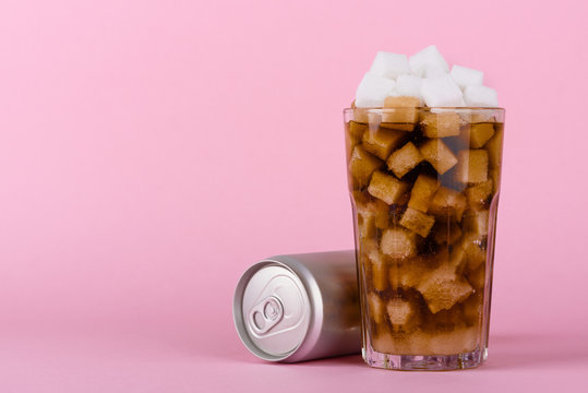 Drinking glass of of lump sugar cubes and soft cola drink with aluminum can on pink pastel background. Unhealthly diet with sweet sugary soft drinks concept.