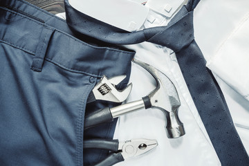 Male business suit bisnizmena pants shirt tie and construction tool wrench hammer in the pocket, the concept of profession