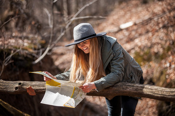 Traveler woman in hat with map in autumn forest, trekking tourism concept
