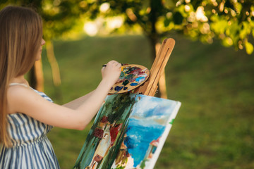 Beautiful girl standing in the park and draws a picture using a palette with paints and a spatula.