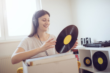 Young woman enjoy music and holding vinyl record
