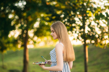 Beautiful girl artist is standing in the park and holding palette with paints