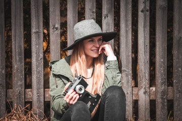 Stylish woman with vintage camera sitting on road at rural country