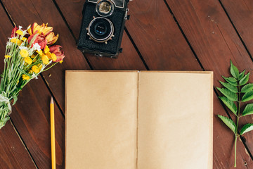 flat lay diary. Top view of notebook paper and camera on a wooden background.