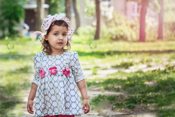Cute little girl in a dress and panama, 2, 3 years old on the meadow in spring day