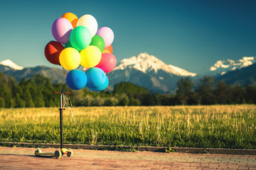 Multicolored balloons kick scooter outdoor festival on blue sky background