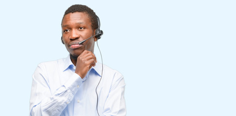 Black man consultant of call center thinking and looking up expressing doubt and wonder