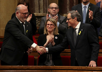 Candidate for the regional presidency of Catalonia, Quim Torra, greets fellow party member Eduard Pujol as Elsa Artadi applauds during an investiture debate at the regional parliament in Barcelona