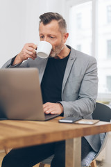 Mature man drinking coffee while working on laptop