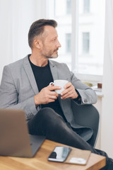 Attractive trendy man relaxing with coffee at home