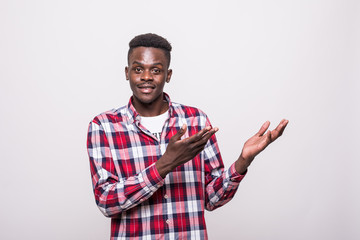 Portrait with empty place afro american man with beaming smile pointing two forefingers to copy space, looking at camera, isolated on grey background