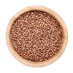 Roasted brown buckwheat grains in wooden bowl isolated on white. Top view.