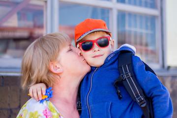Grandma kisses her grandson. Fashionable dressed boy with grandmother_