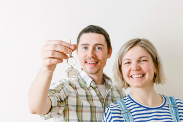 Photo of woman and man with keys from apartment against blank wall