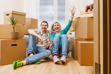 Image of happy couple sitting on couch among cardboard boxes