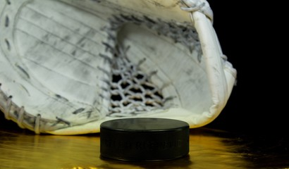 Hockey puck with the inscription `Czech Republic` on the golden background in front of goalie catcher.Black puck on golden background in front of white goalie catcher. We want gold medal.
