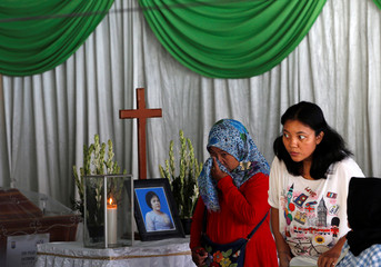 Relatives of victims pray near a coffin of Sri Puji Astutik, who died at a church during Sunday's attack in Surabaya