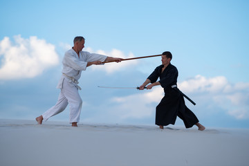 Two concentrated men, in Japanese clothes, are practicing martial arts