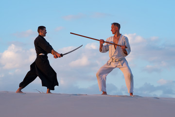 Men are practicing martial arts with traditional Japanese weapon