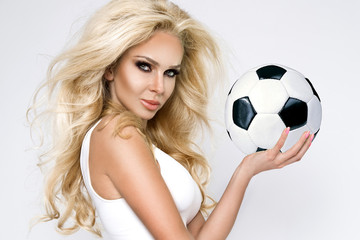 Beautiful, sexy blond woman dressed in sports clothing, gra w football.