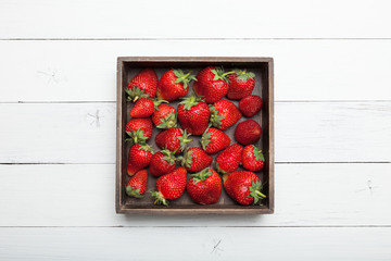 Fresh red strawberry in box, ripe berry pile.
