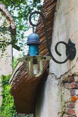 Old lamp, lantern, at brick wall of house outside close-up