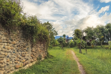 lovely romantic picture of a road to a traditional blue house in thailand