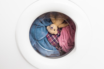 Wild Carousel Ride / Window door of washing machine with laundry and toy teddy bear inside who takes a look out (copy space)