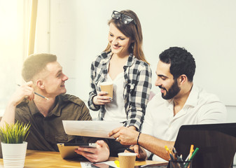 Slender caucasian girl brings collection of pictures to male colleagues, discussing done work together at brown square table