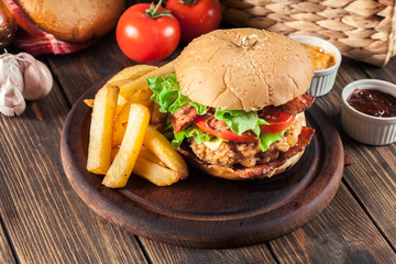 Delicious burger with chicken, bacon, tomato and cheese