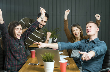 Thrilling reaction of it team to great success, four young workers feeling really happy, indoor slowmotion in small modern office
