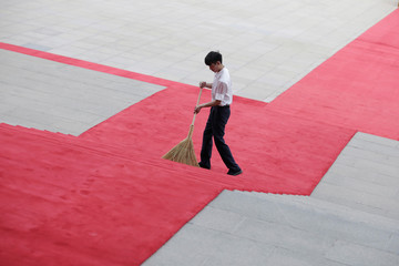 A staff member cleans the red carpet ahead of a welcoming ceremony outside the Great Hall of the People in Beijing