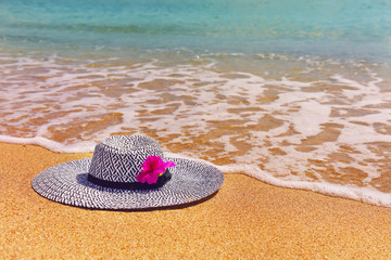 A beach hat on a sunny beach with emerald water. Atmosphere of rest.