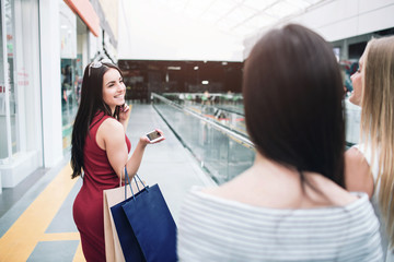 Cheerful and beautiful girl in red dress is looking back to her friends and smiling. Also she holds two bags and phone in her hands. She looks happy.