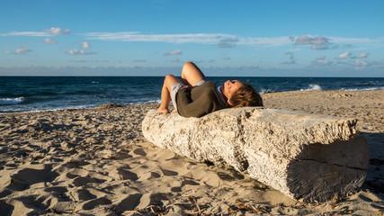 A woman lies on a log in Sardinia and enjoys the sun