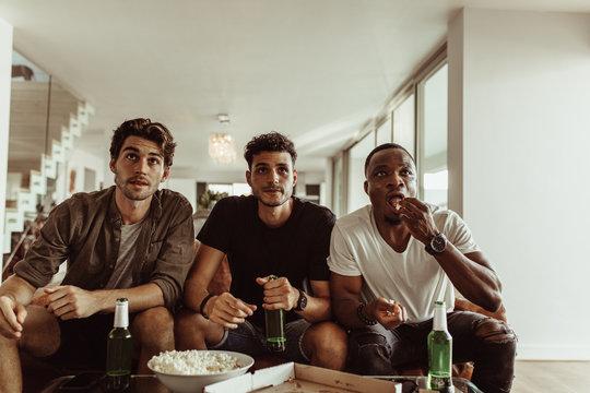 Friends watching a sports match on tv
