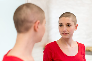 Young adult female cancer patient looking in the mirror.