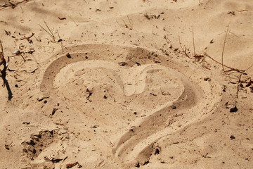 Cute silhouette of heart drawn on dirty sand of beach.