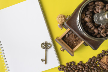 top view flat layer coofee hipster life stlye set, coffee beans, grinded beans in vintage wooden coffee grinder, blank book  and vintage key on yellow modern background