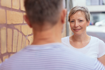 Attractive smiling woman chatting to a male friend