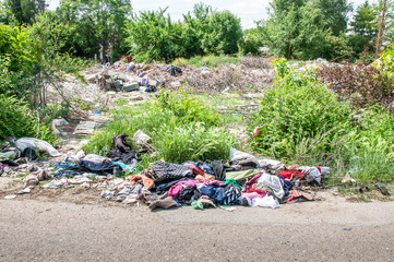 Big pile of junk and garbage dumped in the nature or park in the city polluting the environment with bad smell