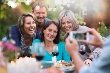 Some friends in their 40s gathered around a table in the garden to share a meal. A man takes a picture of a group of friends