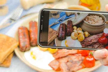 Man taking photo of traditional full English breakfast on smartphone. Taking food photo with mobile phone.