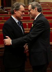 Newly elected Catalonia regional president, Quim Torra, shakes hands with former Catalan president Artur Mas following an investiture debate at the regional parliament in Barcelona