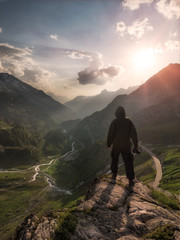 one man calmly standing at the front of cliff overlooking the swiss alps mountain range and sunset