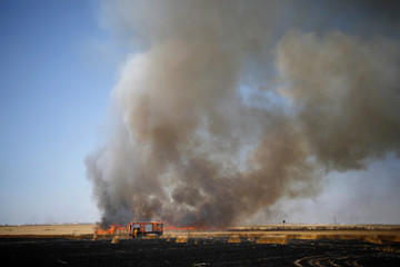 A fire truck is seen in a burning field on the Israeli side of the border fence between Israel and Gaza near kibbutz Mefalsim