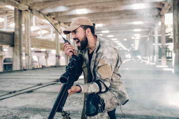 A picture of emotional and adult soldier screaming in portable radio. He is holding it in right hand. There is a big rifle in left one. Man wears military uniform. He is in hangar.